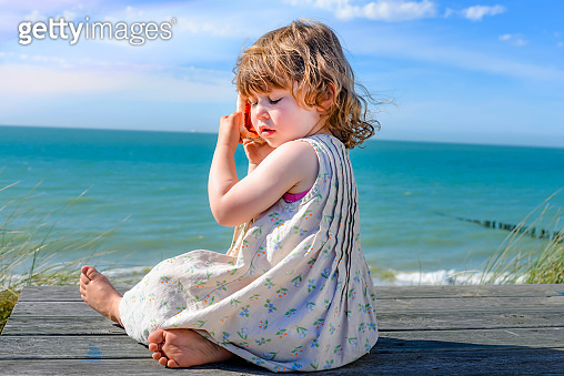 beautiful little girl playing with her seashell