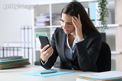 Sad executive reading bad news on phone at office