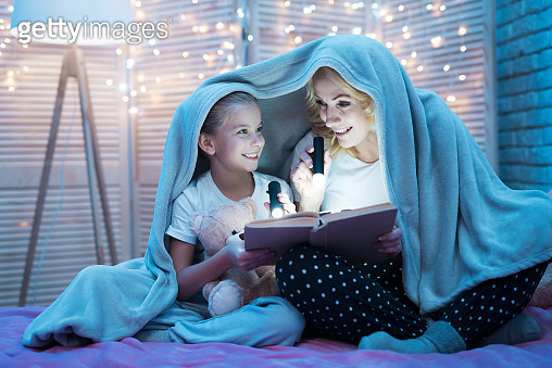 Grandmother and granddaughter are reading fairy tales under blanket at night at home.