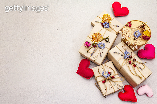Zero waste gift concept. Valentine Day or Birthday eco friendly packaging. Festive boxes in craft paper with different organic decorations. Stone concrete background