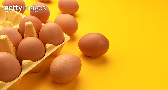 Brown chicken eggs in cardboard box on yellow background