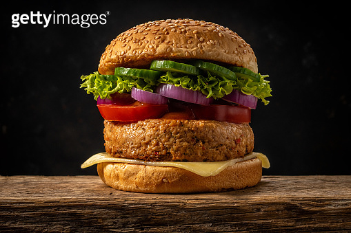 View of fresh tasty burger on wooden rustic table. Food background.