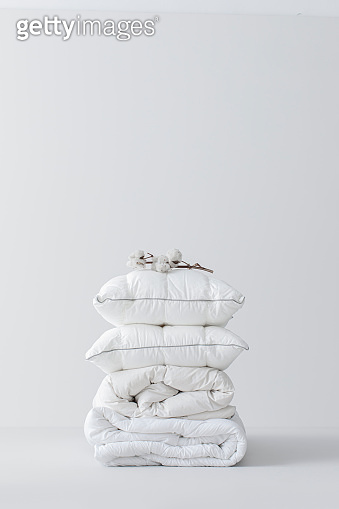Pile of Fluffy White Cotton Pillows and a Duvet With a Cotton Branch Atop (Copy Space)