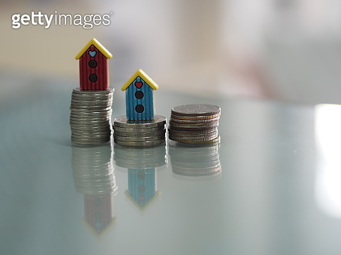 model little home put on the stacked coins