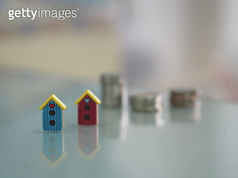 model little home put front the stacked coins