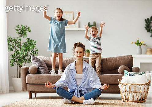 Tranquil young mother practicing yoga to stay calm with mischievous kids at home
