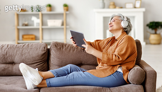 Cheerful senior woman using tablet and listening to music