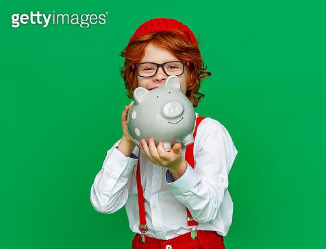 Happy boy storing money in piggy bank