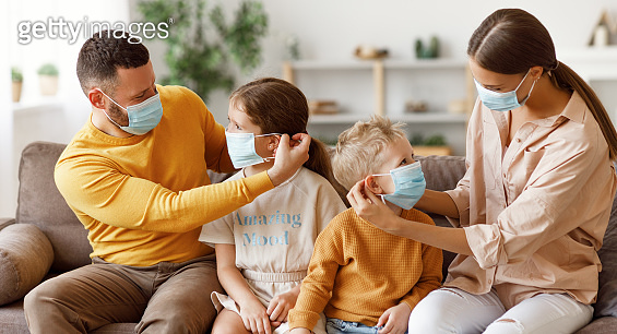 concept of prevention of coronavirus infection. happy family: caring parents put protective medical masks on their children  in  midst of the coronavirus pandemic at home