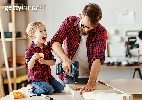 Happy kid helping father in carpentry studio