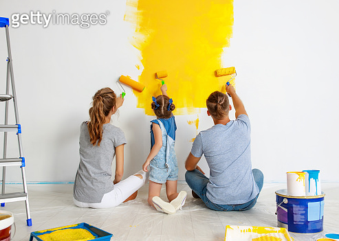 Repair in apartment. Happy family mother, father and child daughter  paints wall