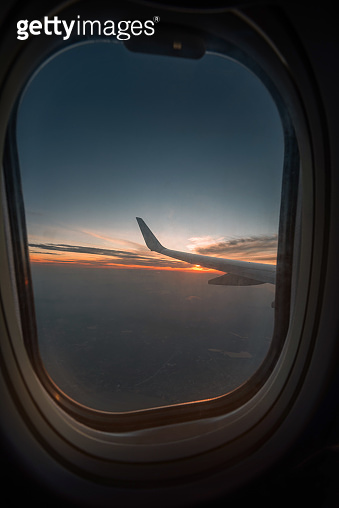 Silhouette wing of an airplane at sunrise view through the window.