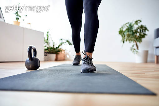 Closeup of female legs with sport shoes during home workout on sport mat