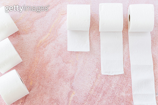 White toilet paper roll on pink background