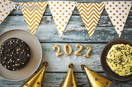 Hanging party flags, cakes and party hats isolated on blue wooden background, decorate items for festival, celebrate event, birthday, Christmas and 2021 New Year background