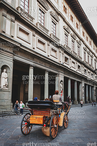 A tourist horse-drawn carriage passing the Uffizi Gallery, an art museum located adjacent to the Piazza della Signoria in the historic centre of Florence, Italy