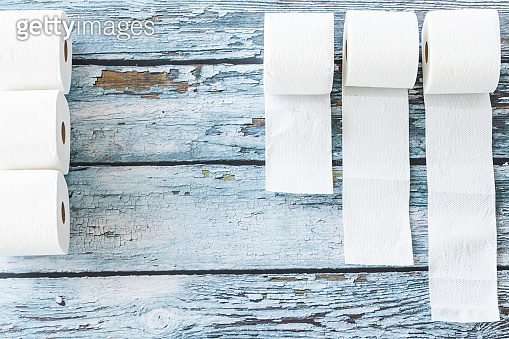 Soft white toilet paper roll on blue wooden background