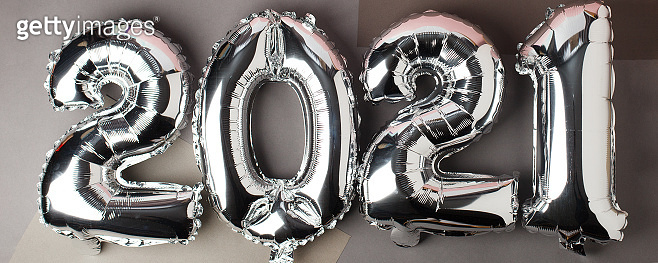 Happy New year 2021 celebration. Silver foil balloons numeral 2021 on gray background. Flat lay, seasonal holiday party decoration, banner, minimal stylish card
