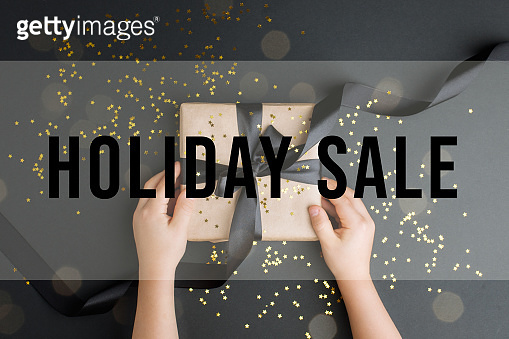 BLACK FRIDAY HOLIDAY SALE Craft gift box on a dark background, decorated with a bow, romantic luxury atmosphere. For seasonal shopping sales, consumer flyers, banner, coupon