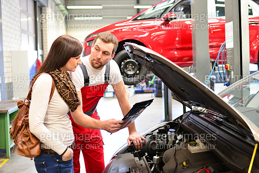 customer service in a garage - mechanic and woman discuss the repair of a vehicle