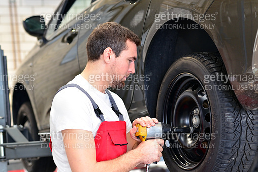professional car mechanic works in a workshop and changes tyres on the vehicle