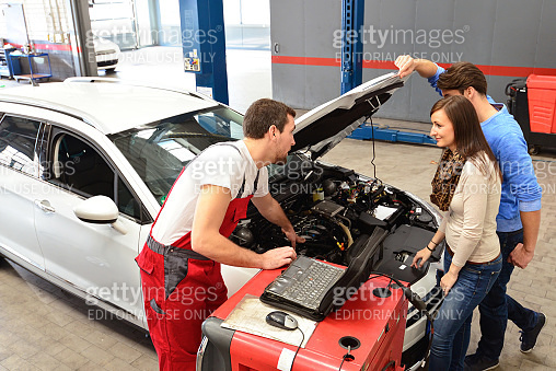 customer service in a garage - mechanic and customer discuss the repair of a vehicle