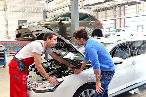 after-sales service in the car repair shop - mechanic and man talk about repairing a vehicle