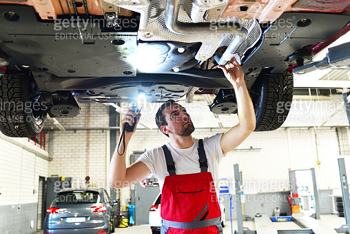 professional car mechanic works in a workshop and repairs vehicles - check the technology, brakes and tires