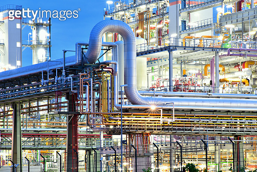 refinery - chemical factory at night with buildings, pipelines and lighting - industrial plant