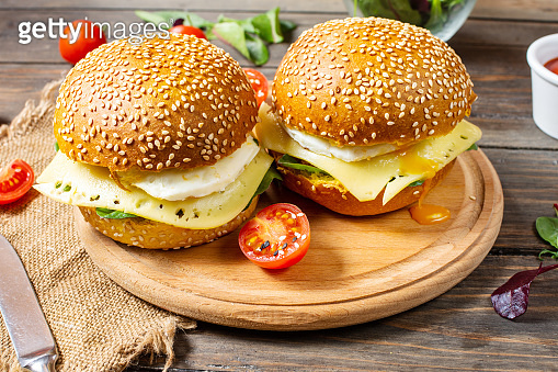 Breakfast two burgers with chicken, fried egg and cheese on rustic wooden background