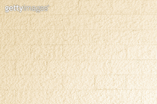 Limestone rock slab tile wall texture patterned background in light pastel cream yellow beige color