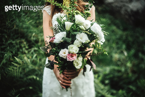 stylish boho bride holding  rustic bouquet of amazing flowers and herbs on background of rocks in mountains