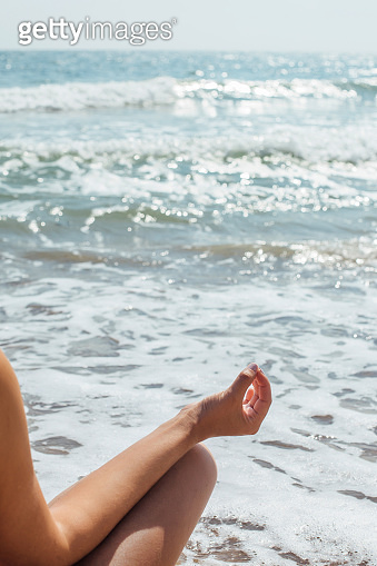 Closeup of woman hand in lotus position on background of sunny waves while practicing yoga and meditating. Yoga and meditation on beach at sea. Mental health and self care