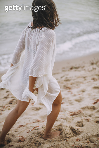 Carefree boho girl in white summer dress walking on beach. Happy young woman relaxing on seashore. Summer vacation. Mindfulness and relaxation. Lifestyle