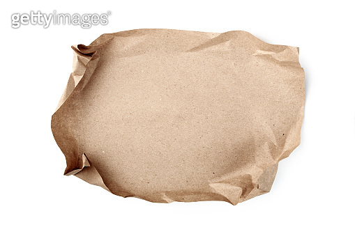 Crumpled sheet of craft paper on white background. Recyclable material.