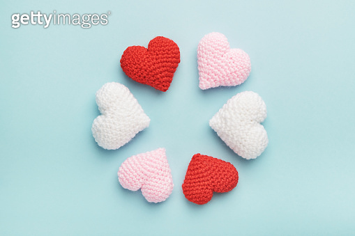 Valentine's day decorative background. Circle of red, pink and white croched hearts on blue.