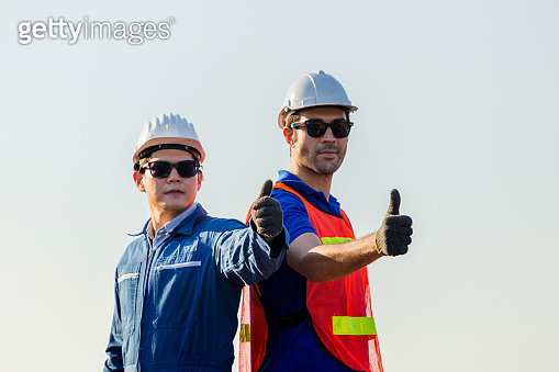 Cheerful factory worker and engineer man smiling with giving thumbs up as sign of Success