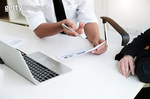 A male business consultant describes a marketing plan to set business strategies for women business owners with using computer. business planning and business researching concept.