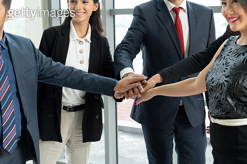 Many happy business people join hands together