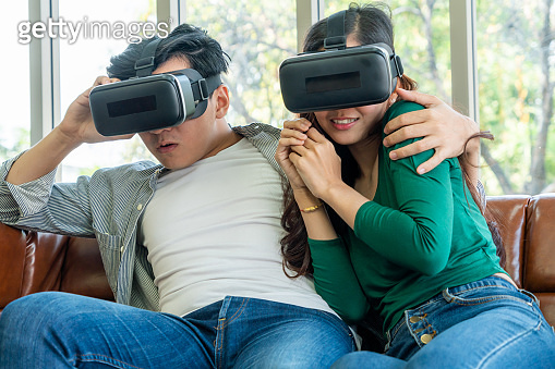 Happy couple watching video in virtual reality VR