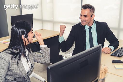 Business people wearing headset celebrate working in office