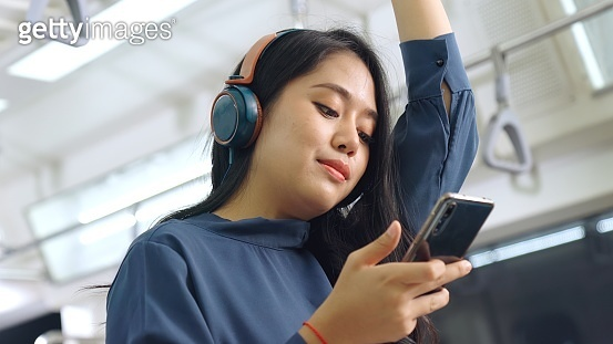 Young woman using mobile phone on public train