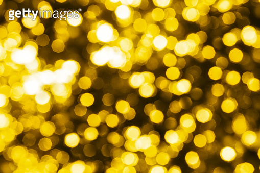 Abstract golden blurred bokeh background, defocused round yellow & white shiny dots texture, beautiful gold glowing pattern, bright holiday lights decorative backdrop, festive sparkling wallpaper