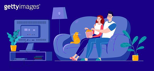A married couple is watching a movie on a big screen, sitting on a sofa at home in a dark room.