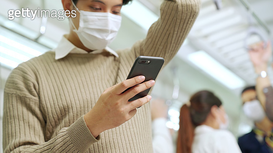 Traveler wearing face mask while using mobile phone on public train