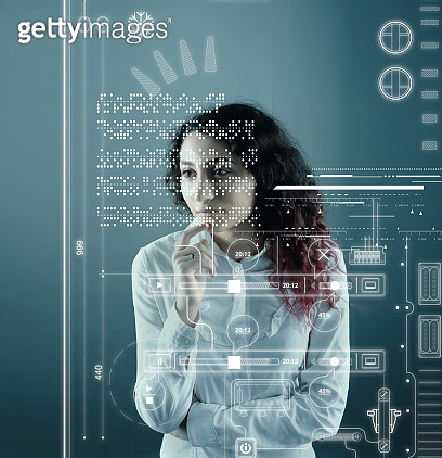 Woman analyze futuristic user interface . High tech screens data and information .