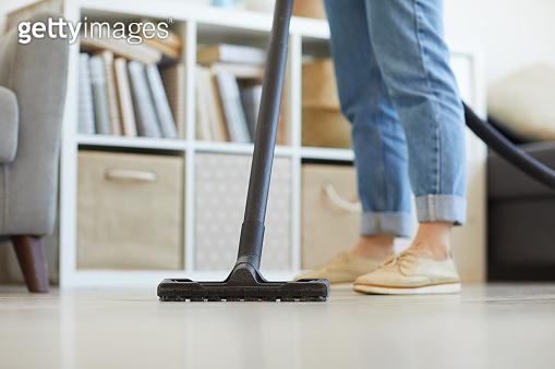 Woman vacuuming at home