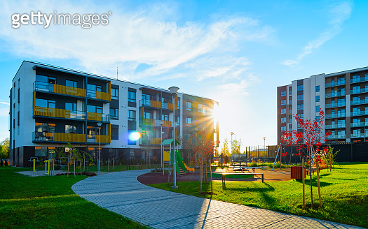 Apartment residential house facade architecture with kids playground sun light reflex