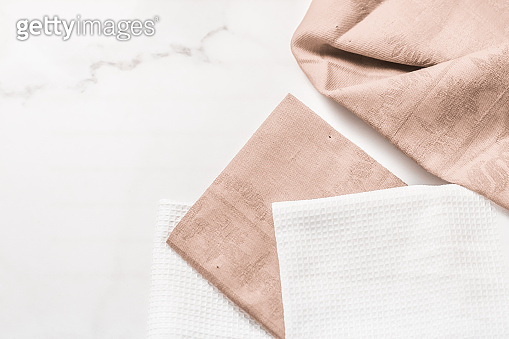 Kitchen textile on chic white marble background, napkin and towel set, folded fabrics as food styling props for luxury home decor brand, interior design