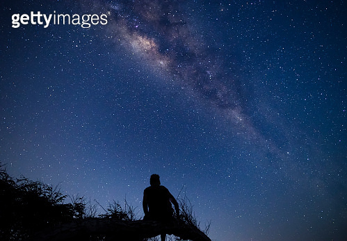 Person sitting on a tree branch at night enjoying milky way and sky full of stars dreamy moment at campsite in Sumbawa